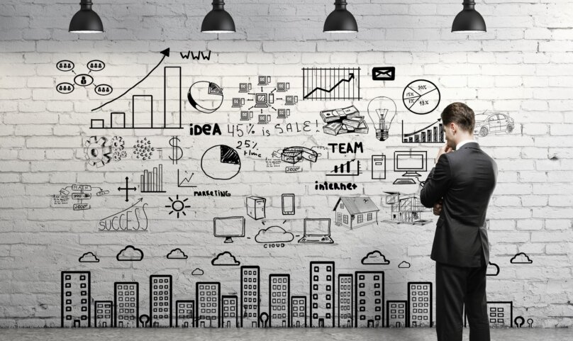 businessman looking at business concept on wall